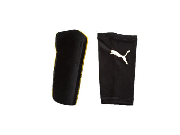 Benskydd från puma och på bilden visas benskyddets baksida som är svart. Bilden visar också en benskyddsstrumpa som är svart med en vit Puma logo.
