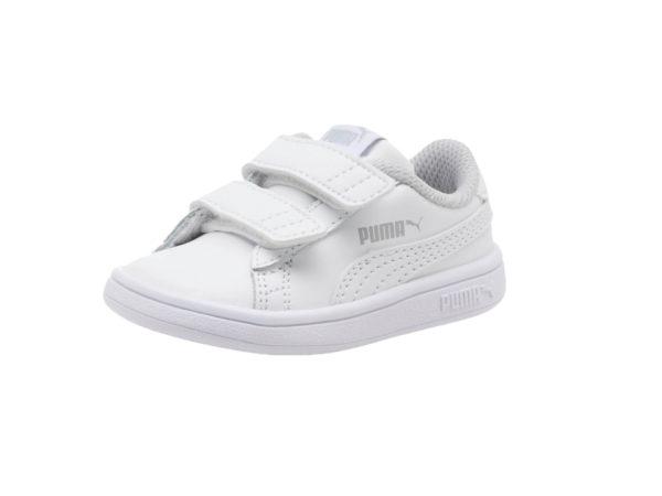 En helvit barnsko med vita kardborreband, samt vita ränder. Det finns en ljusgrå logo på sidan av skon. på bilden visas sko på sidan.