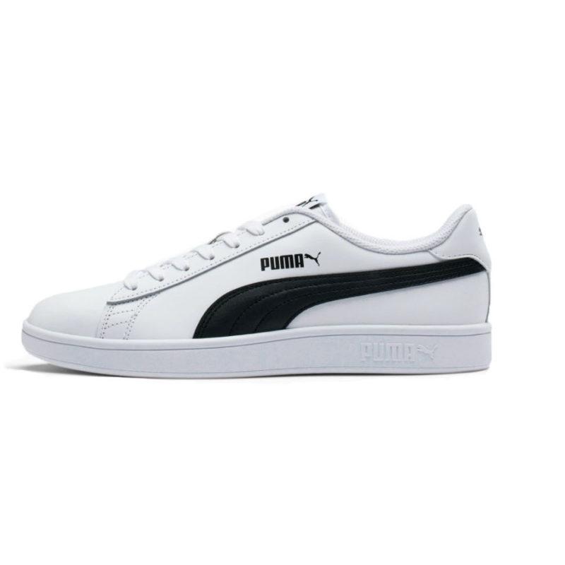 En vit sko med vita snören och svarta ränder. Det finns en svart logo på sidan av skon. På bilden visas skon på sidan.